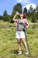 Woman hiker drinking water from a bottle in the mountain