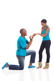 African man putting engagement ring on his girlfriend after she