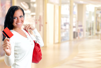 Young pretty woman in shopping center with credit card