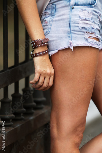 Leather bracelet with spikes and torn jeans