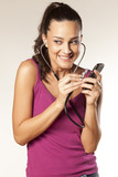 young beautiful smiling girl uses a stethoscope to tap phones
