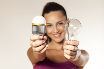 girl holds the old and the new generation of light bulbs