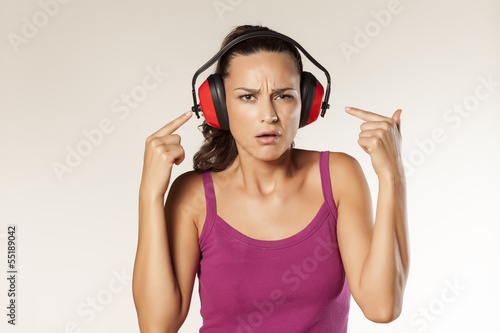scowling brunette can not hear because of the anti loud headset