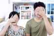 Asian couple cover faces at home