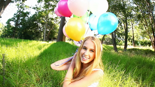 Video of a beautiful woman smiling while holding balloons.