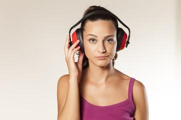 beautiful wierd young brunette posing with anti loud headset
