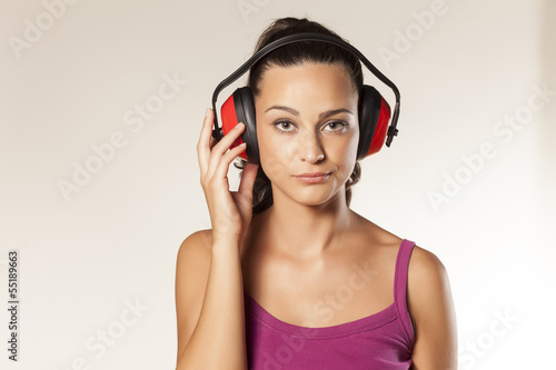 beautiful wierd young brunette posing with anti loud headset