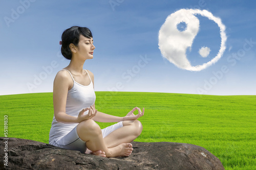 Beautiful girl exercise yoga with ying yang cloud