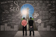 Business partners and SEO doodle on blackboard
