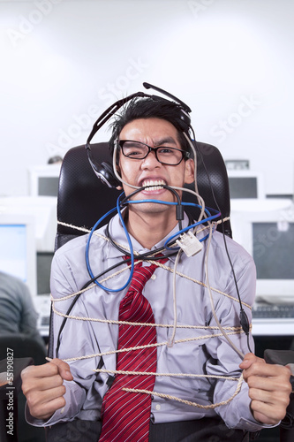 Stress businessman tied in rope at office