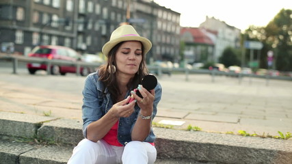Woman applying lipstick on her lips in the city