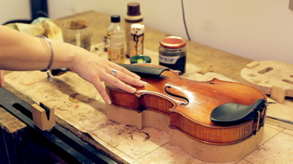 Music repair lab girl caressing violin