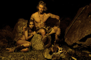 Primitive man and his woman sitting near the fire in the cave