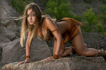 Sexy primitive woman standing on a rock