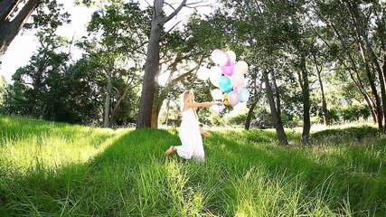 Beautiful woman smiling while joyfully walking with balloons