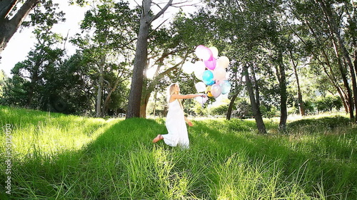 Beautiful woman smiling while joyfully walking with balloons