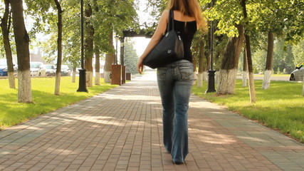 A young girl in a park. Walk down the avenue