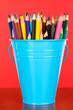 Color bucket with multicolor pencils, on color background