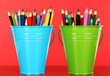 Color buckets with multicolor pencils, on color background