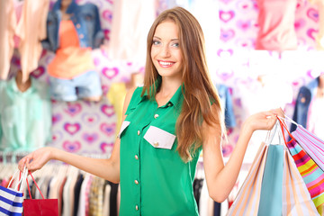 Beautiful young woman in shop with shopping bags