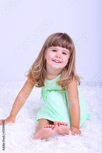 Little cute girl sitting on carpet, on gray background