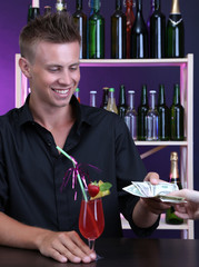 Portrait of handsome barman receiving tips from client
