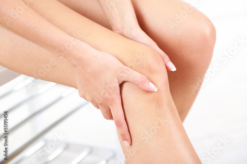 Girl with sore foot on gray background