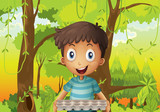A boy holding an empty eggtray in the forest