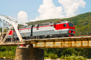 Train rides over bridge across mountain river