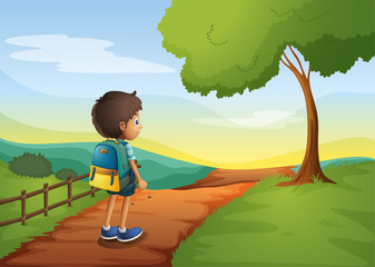 A boy walking while carrying a bag