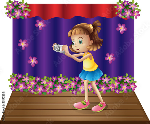 A stage with a young girl holding a camera