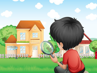 A boy with a magnifying glass studying the grasses