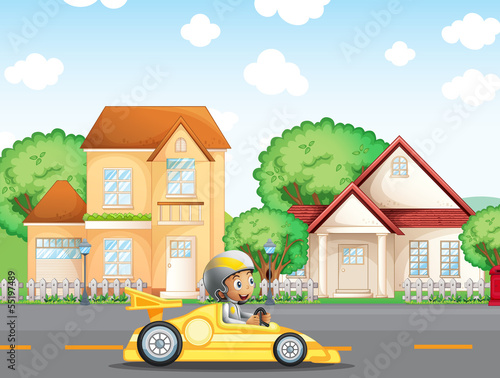 A boy in his racing car across the neighborhood