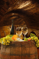 Vine cellar with glasses of white vine against barrels