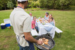 Father in chefs hat and apron cooking barbecue for his family