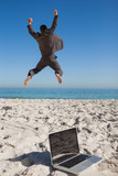 Victorious businessman in suit jumping leaving his laptop