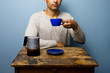 Young man at wooden table drinking cofffee