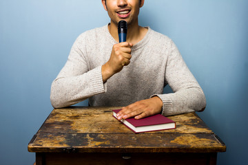 Man with book is speaking into microphone