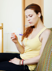 Unhappy serious  woman with pregnancy test