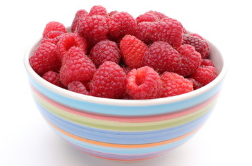 Fresh raspberries with a bowl on a white background