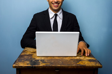 Happy businessman with laptop at old table