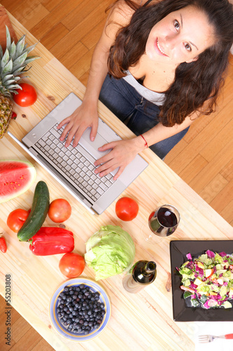 Woman using a Laptop while cooking