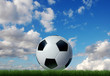 Soccer ball on grass with sky and clouds on background.