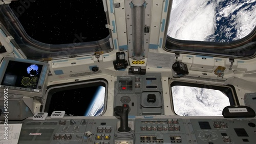 View of the space shuttle cockpit orbiting earth.