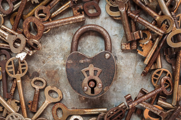 Vintage rusty padlock surrounded by old keys