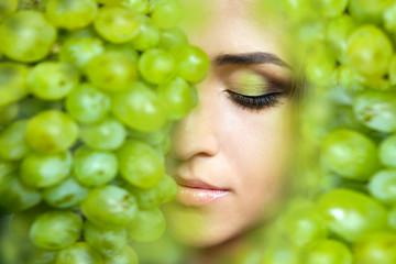 Девушка с красивым макияжем и виноградом