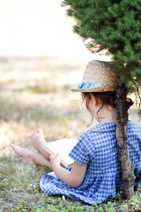 Little girl reading a book in a meadow
