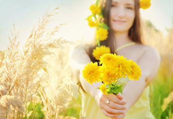 Pretty girl holding bouquet in the sunny summer grass field