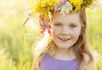 Happy little girl in flower crown on sunny summer meadow