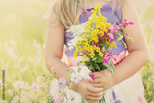 Little girl with flowers on grassy field